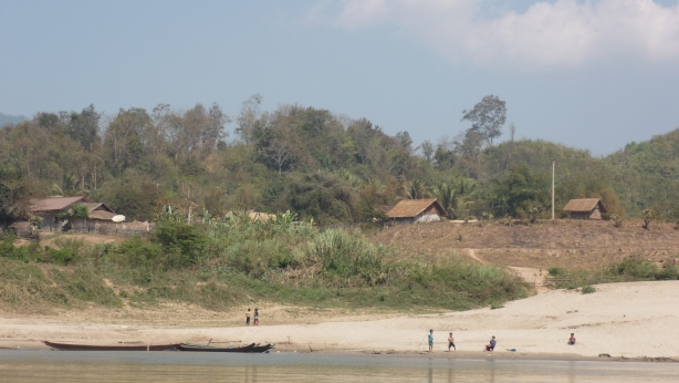 Passing a local Lao village in the slow boat along the Mekong River in Laos