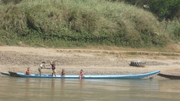 Village children playing and waving at slow boat tourists on the Mekong River in Laos