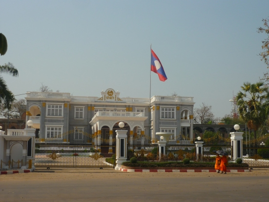 Lao Presidential Palace with passing monks in Vientiane, Laos