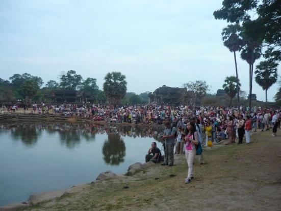 Camera-clad tourists awaiting 'sunrise-splendour' of overcast Angkor Wat near Siem Reap, Cambodia