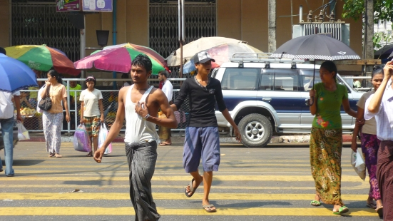 Hustle and bustle to cross the street: women with sun-brellas and a man in his longi in Yangon, Myanmar