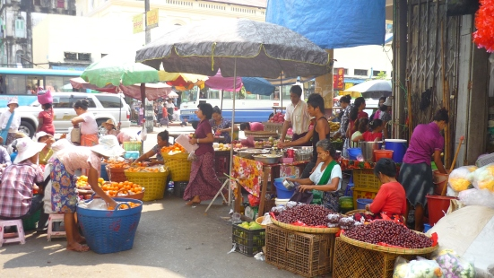 Women wearing thanaka sunscreen whilst selling fresh goods in the streets of Yangon in Myanmar