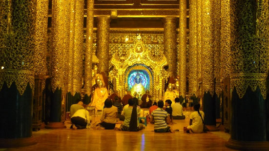 Locals praying within Shwedagon Pagoda in Yangon in Myanmar