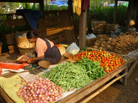 Burmese market trader selling vegetables in Kalaw morning market in Myanmar