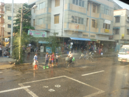 Children spraying man on bicycle with water during Yangon's Water Festival in Myanmar