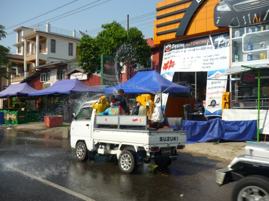 Open-top van filled with local Burmese seeking water blessings on the road in Yangon, Myanmar